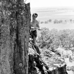 1981. December. Mike Law having topped out of Debutantes and Centipedes (25) on Lois Lane Wall after his first ascent. Mt Arapiles. He is pointing to his lactic acid burning forearms!