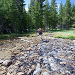 Karen crossing a stream in Lyell Canyon. John Muir Trail, the Sierra Nevada Mountains in California, United States.
